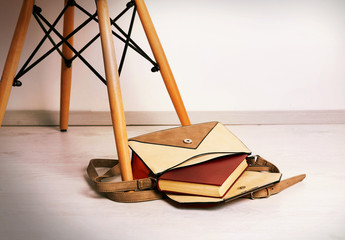 Fashion female handbag with book on a floor