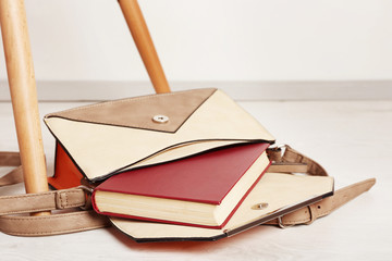 Fashion female handbag with book on a floor, close up