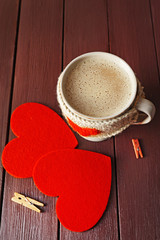 Coffee cup with milk, clothespins and two hearts on wooden background closeup