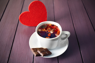 Cup of fruit tea with red heart and piece of chocolate on wooden background, closeup