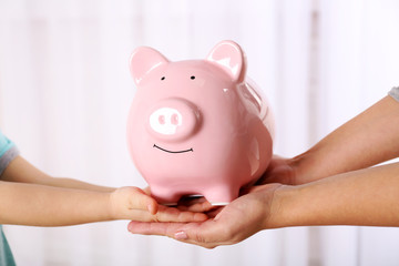 Savings concept. Piggy bank in parent and child hands