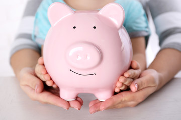 Savings concept. Hands holding piggy bank, close up