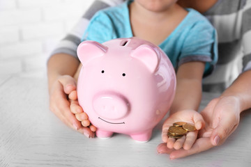 Savings concept. Hands holding piggy bank and pile of coins, close up