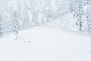 scenic view of small people walking in snow mountain.