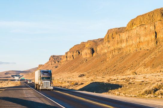 a big truck driving in the sunset with mountain background.