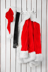 Santa jacket, hat and belt on a wooden white wall