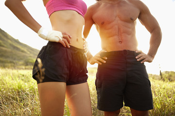 Couple in sportswear standing with hands on hips in rural field