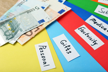 Distribution of money, financial planning, euro and bright envelopes, on wooden table background
