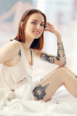 Attractive woman with tattoo sitting on the bed