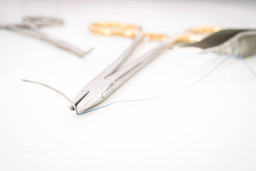 Close up of needle holder with suture and needle, forceps and su