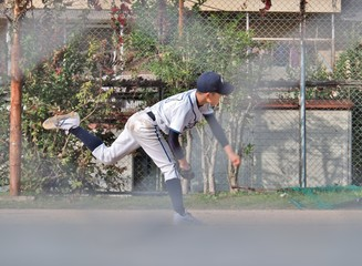 Young Japanese baseball player no.17 pitching by left hand. This photo was taken through a wire mesh fence.