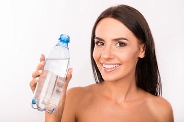 Slim cute young girl holding a bottle with water