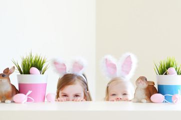 Two adorable sisters wearing bunny ears on Easter day