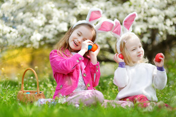 Two adorable little sisters playing with Easter eggs on Easter day