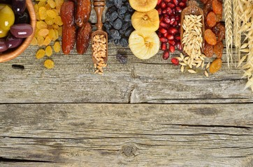 Mix of dried fruits, barley, wheat, olives, pomegranate on wooden table - symbols of judaic holiday Tu Bishvat. Copyspace background.Top view