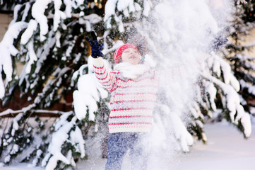 Adorable school aged kid girl in colorful sweater and hat playing in the snow on beauty winter day