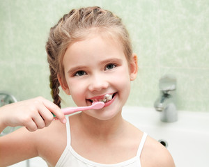 Smiling cute little girl brushing teeth in bathroom