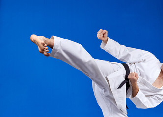 On a blue background athlete beats kicking