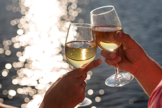 Happy couple drinks champagne on a yacht