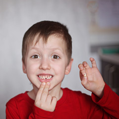 Portrait cute  little Boy shows the First dropped-out milk Tooth