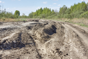 Old broken dirt road with rubbish and wood. Holes and grooves. Russia