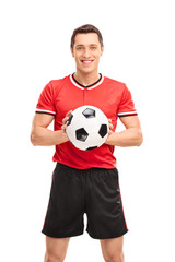 Young football player holding a ball
