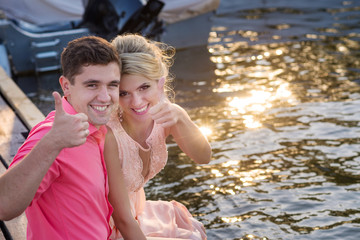 Young beautiful couple is sitting on a berth near the water in yacht club