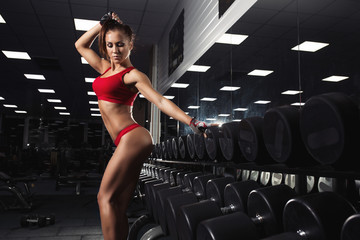 Sexy young woman posing after exercises in gym. Fitness athletic brunette girl