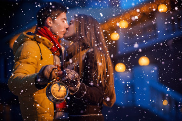 Couple with clock in winter night