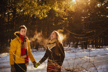 Happy couple walking in winter forest