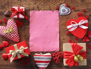 Pink paper in different hearts on wooden background. Valentines Day background