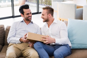 Smiling man offering gift to his boyfriend in living room