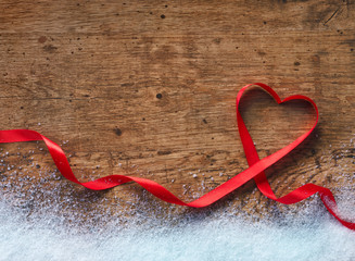 Happy Valentines Day. Red Ribbon Heart with snow on a wooden background. Valentines Day concept