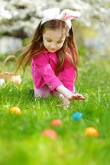 Adorable little girl hunting for easter egg on Easter day