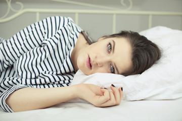 Portrait of beautiful girl lying in bed