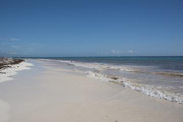 barca al largo di una spiaggia caraibica con mare dai colori turchesi