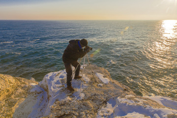 Photographer on the rocks taking beautiful landscape pictures