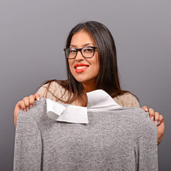 Portrait of a woman choosing clothes against gray background