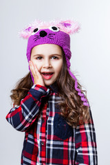 A little girl is in the cap of mouse. Studio photo