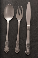 Spoon, fork and knife on black background