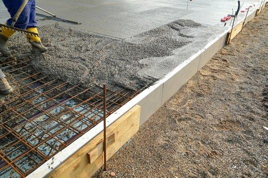 Baubranche - Verteilen von Fertigbeton für eine Fundamentplatte