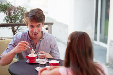 Young man and woman drinking coffee outdoor and having a chat on