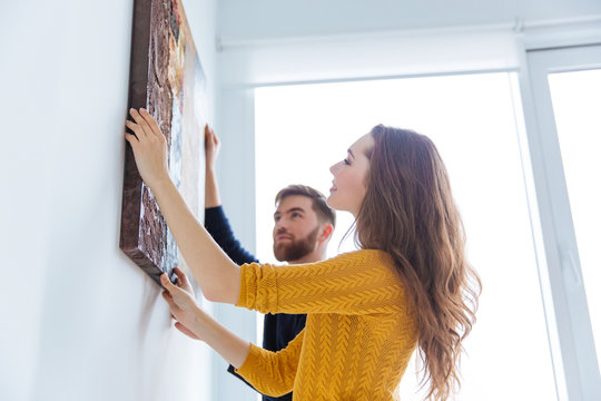 Couple hanging picture on the wall
