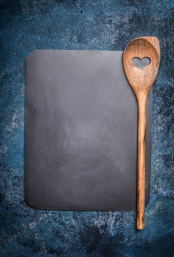 Blank chalkboard with cooking spoon on rustic background, top view. Restaurant or cafe menu. Template design for  recipes or ingredients shopping list.