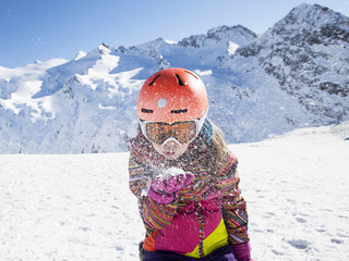 Portrait of skier girl blowing snow from the palm in Alps mounta