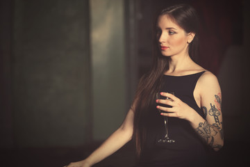 Beautiful young woman with tattoos holding glass of wine, retro stylization