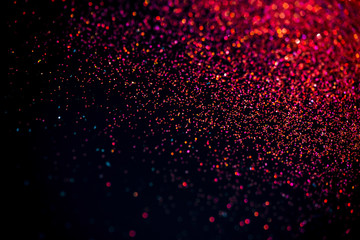 Red shiny glitter on black background. Macro shot, shalow DOF.