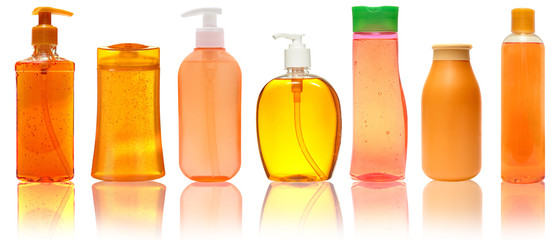 Seven orange  Plastic Bottles With Shampoo, Liquid Soap, Shower Gel. Isolated on white background with reflection.