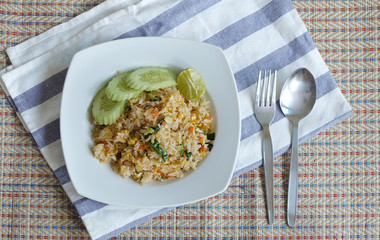 Pork fried rice serving with lime and cucumber