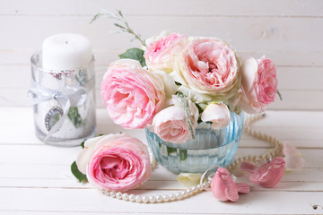 Pink roses flowers  in blue vase on white painted wooden backgro
